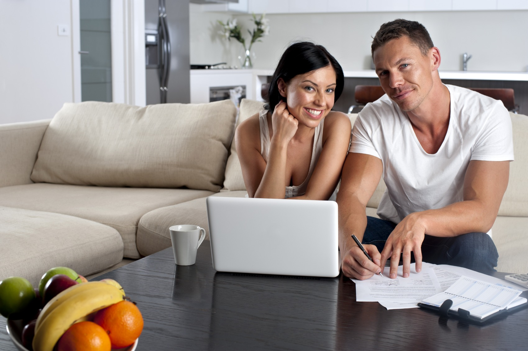 Couple doing paperwork with a laptop computer on the sofa