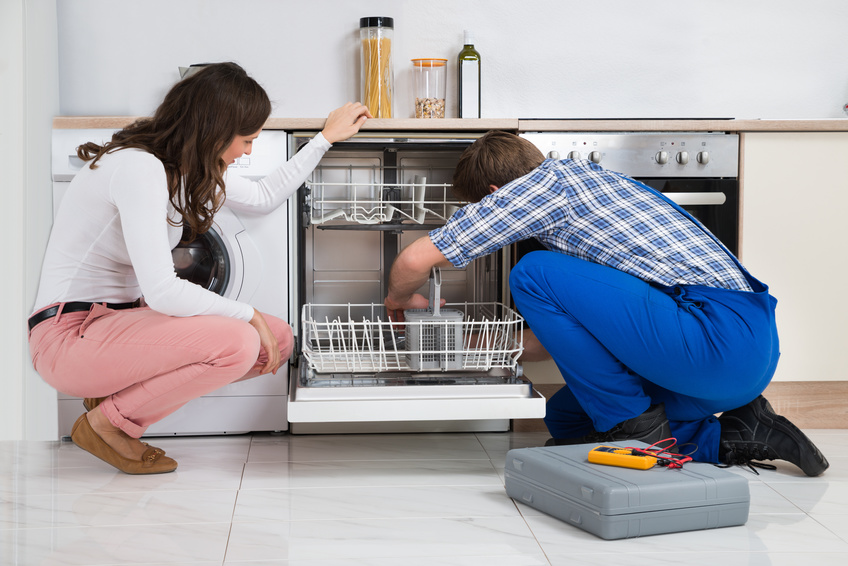 Young Woman Looking At Repairman Repairing Dishwasher In Kitchen