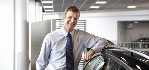 Salesman standing with new car in showroom