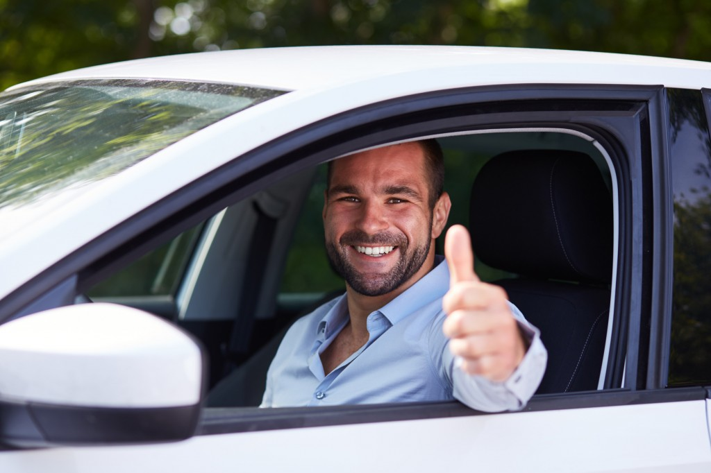 Man driving his car and makes gesture with thumb up