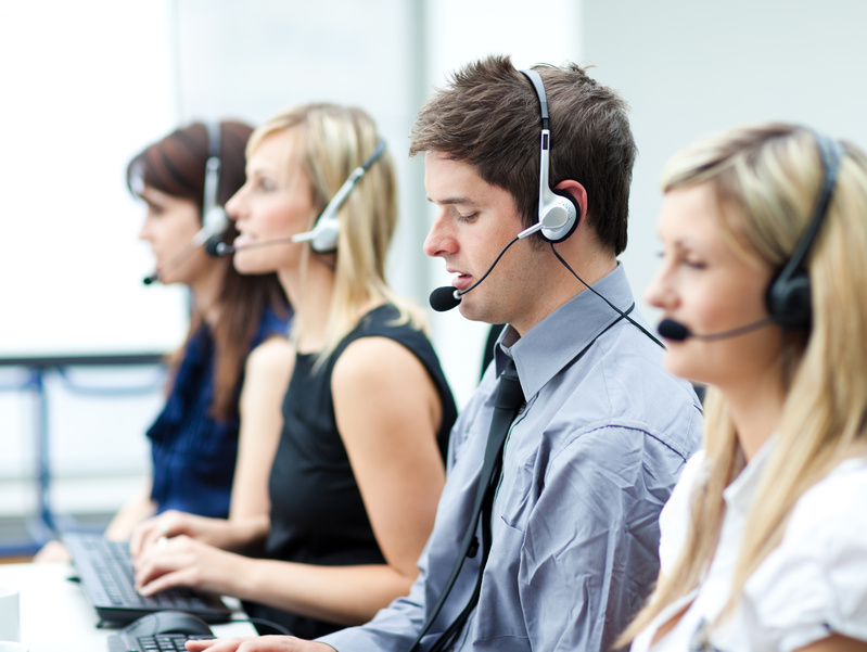 Attractive young man working in a call center with his colleagues